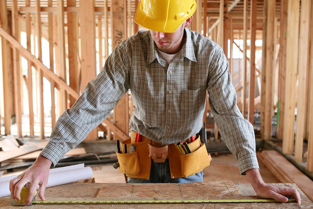 A man working building a home and measuring some wood